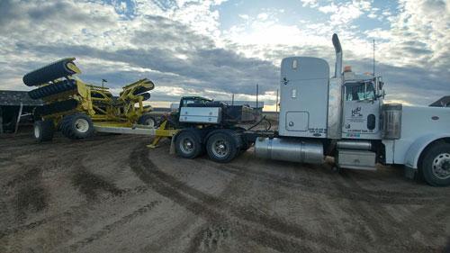 semi transporting farm equipment